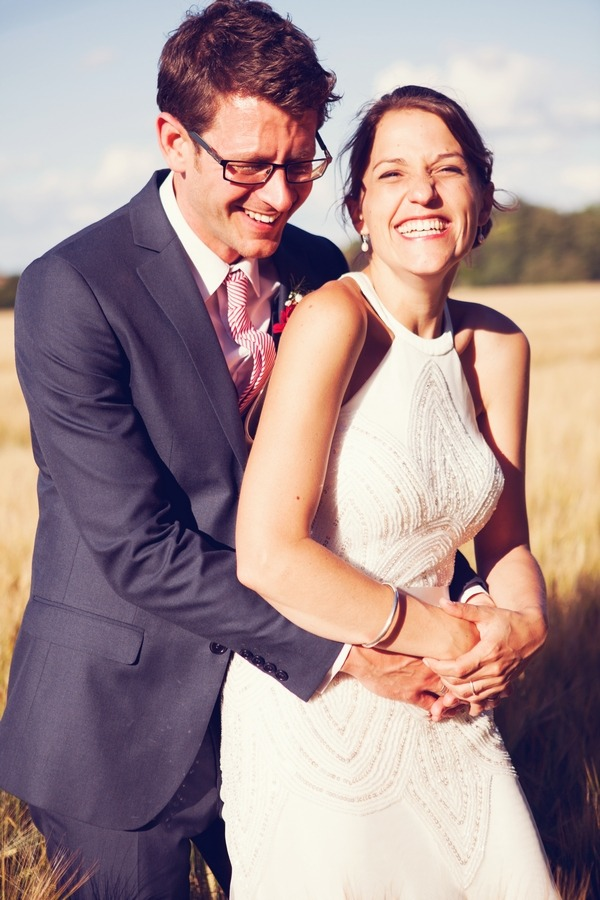 Bride and groom laughing together in field
