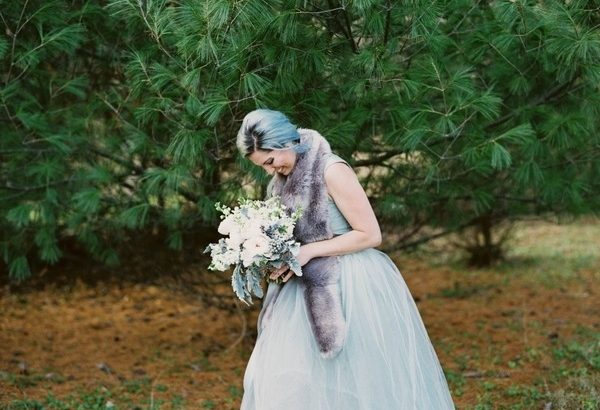 Bride with blue hair looking down at bouquet