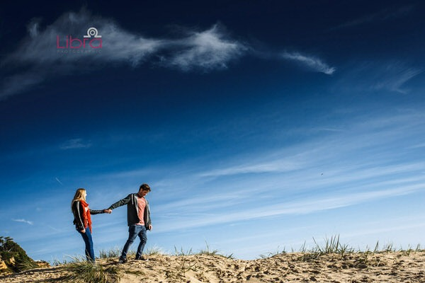 Couple holding hands on Branksome Beach