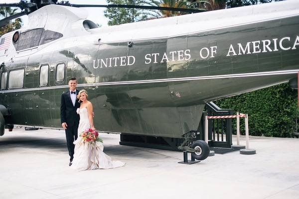 Bride and groom in front of military helicopter