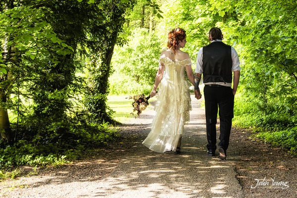 Bride and groom holding hands walking down country lane - Picture by John Young Photography