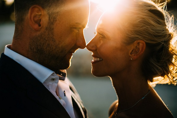 Bride and groom face to face with sun shining between them - Picture by Albert Palmer Photography
