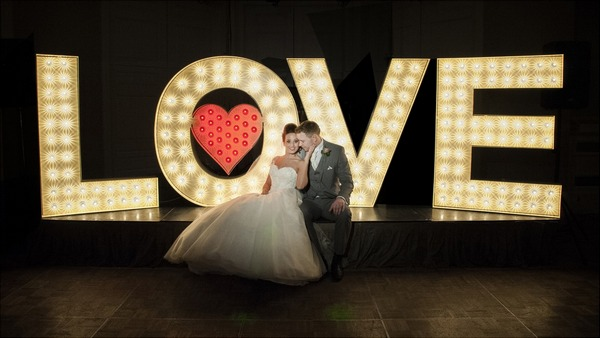 Bride and groom sitting in front of large illuminated LOVE letters - Picture by Image-i-Nation Photography