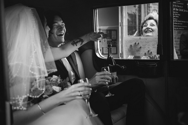 Woman holding marriage certificate against wedding car window as groom laughs - Picture by Linus Moran Photography