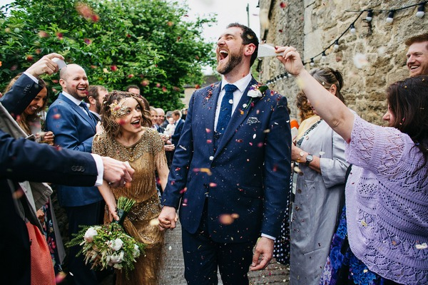 Groom laughing as guests throw confetti over him and bride - Picture by John Hope Photography