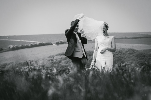 Bride laughing as groom tries to adjust her veil - Picture by Alexa Poppe Wedding Photography