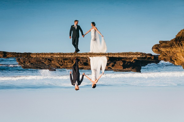 Reflection of bride and groom in sea - Picture by Estefania Romero Photography