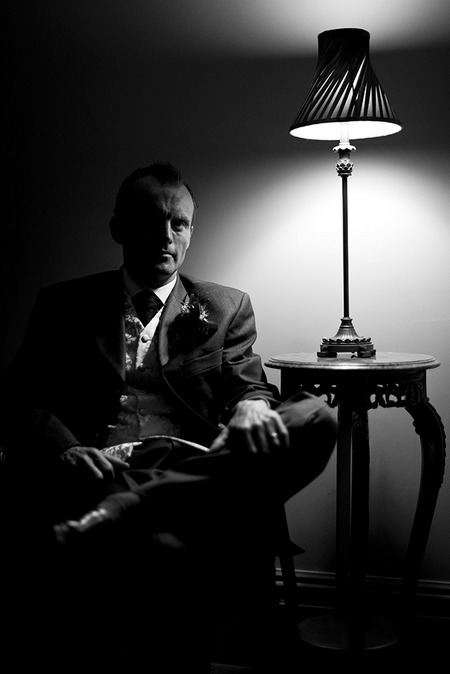 Black and white picture of groom sat in chair next to lamp - Picture by Matt Selby Photography