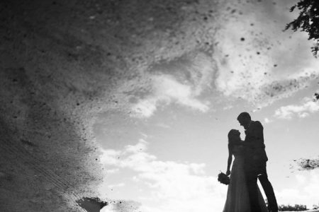 Reflection of bride and groom in puddle - Picture by Jay Emme Photography
