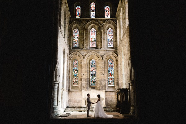 Bride and groom holding hands in church with light shining down on them - Picture by Andy Turner Photography
