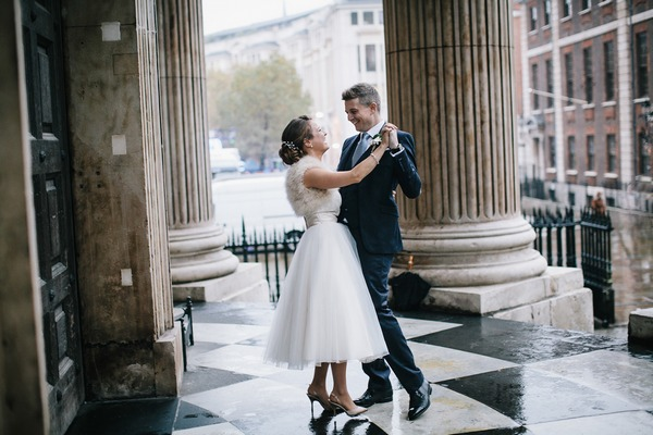 Bride and groom dancing in the rain at entrance to wedding venue - Picture by My Beautiful Bride