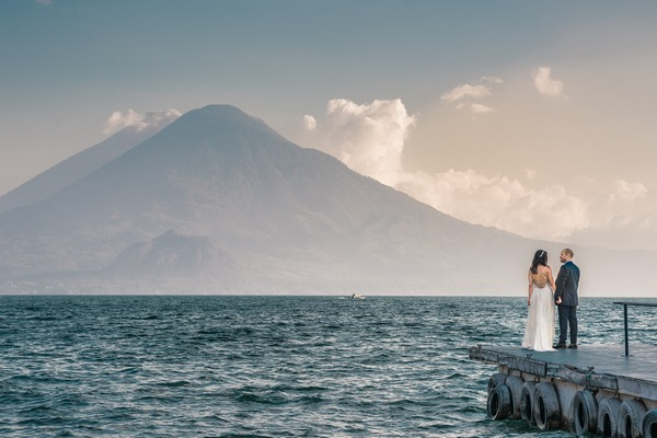 Bride and groom standing on jetty with sea and mountains in front of them - Picture by Daniel Lopez Perez