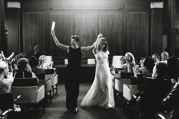 Delighted brides with arms in the air as they leave wedding ceremony - Picture by Lyndsey Goddard Photography