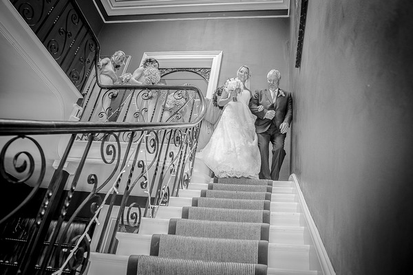 Father leading bride down the stairs