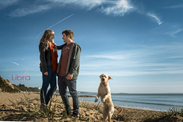 Couple on Branksome Beach with dog jumping into picture