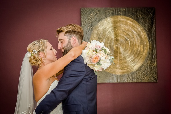 Bride and groom in front of picture