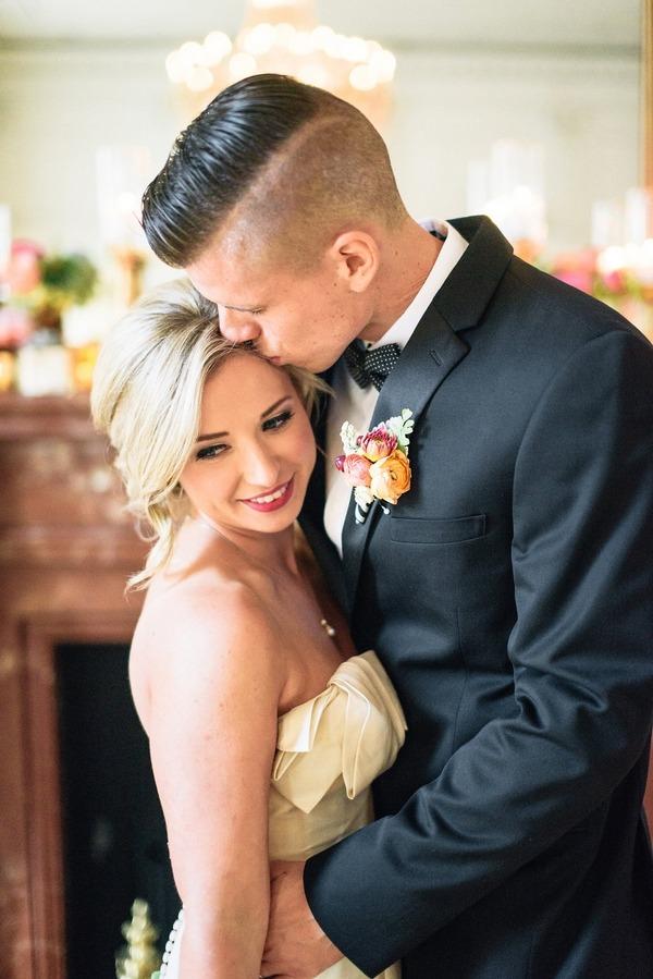 Groom kissing bride on head