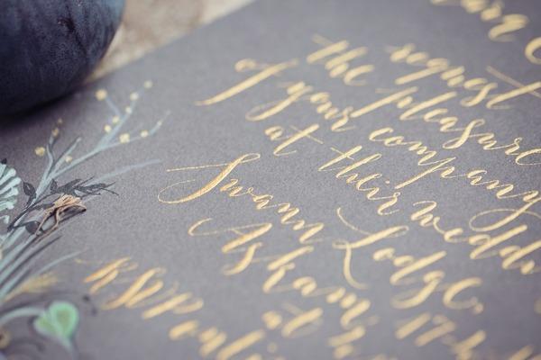 Gold calligraphy on slate wedding stationery