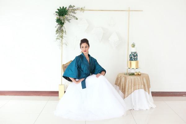 Bride sitting next cake table