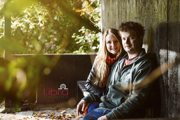 Couple sitting on bench in shelter