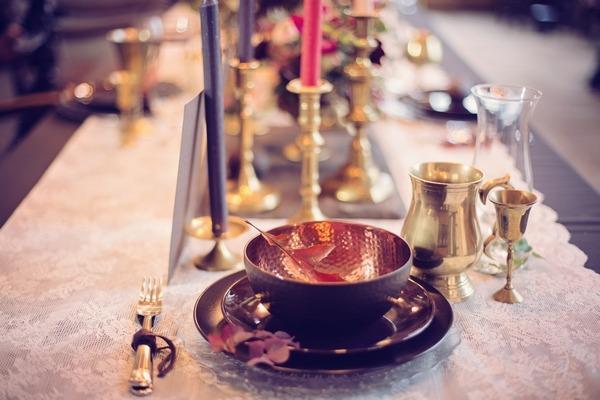 Wedding place setting with brass and dark crockery
