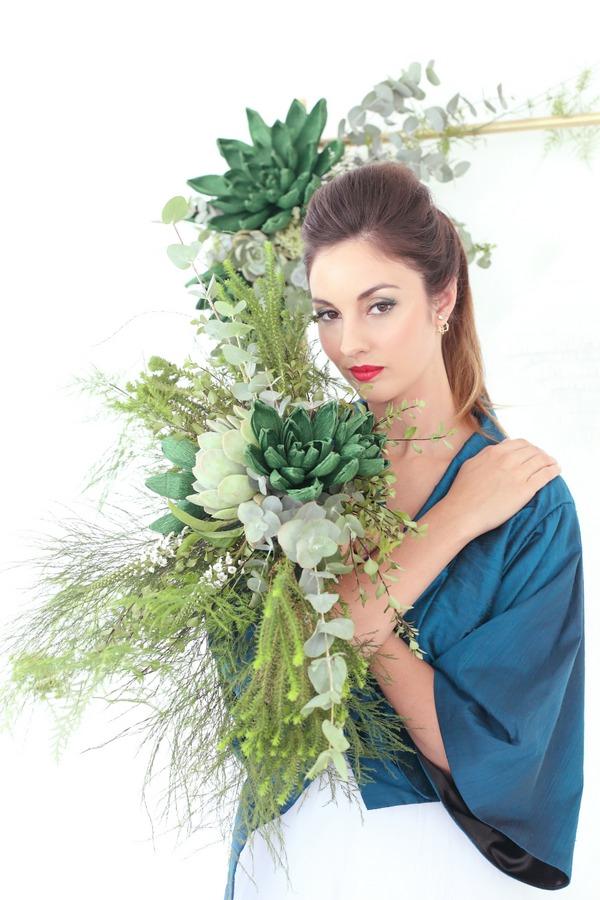 Bride holding succulents and foliage bouquet