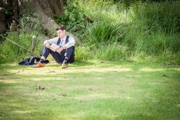 Best man sitting on grass practising speech