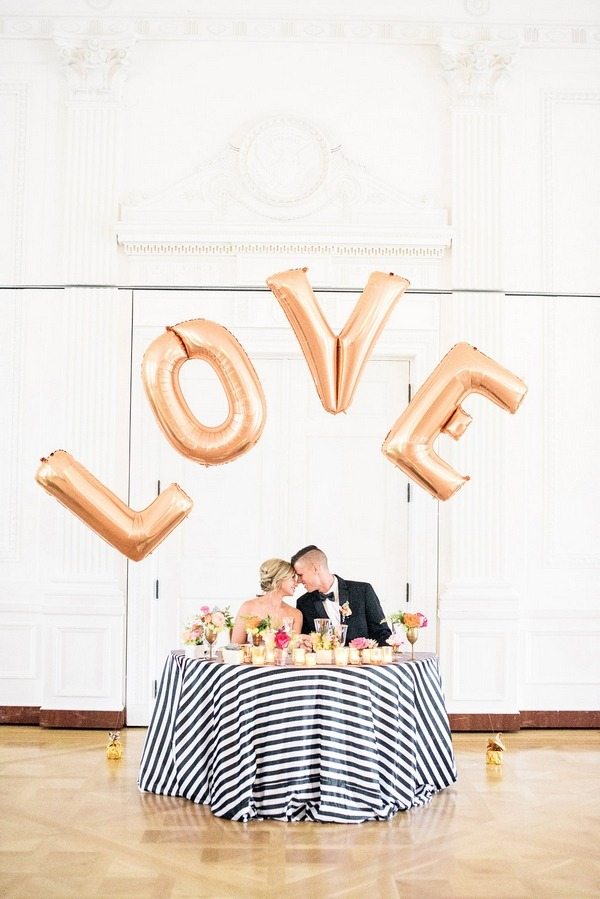 Bride and groom kissing behind LOVE letter balloons