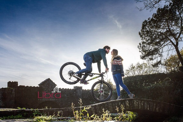 Man on front wheel of mountain bike kissing his fiancée