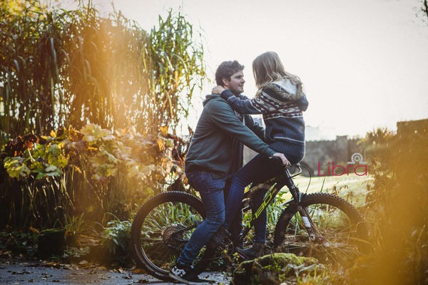 Woman sitting on handlebars of partner's mountain bike