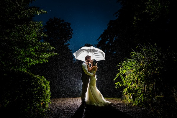 Bride and groom kissing under umbrella in rain - Picture by Libra Photographic