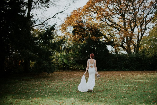 Bride walking across garden of Deer Park