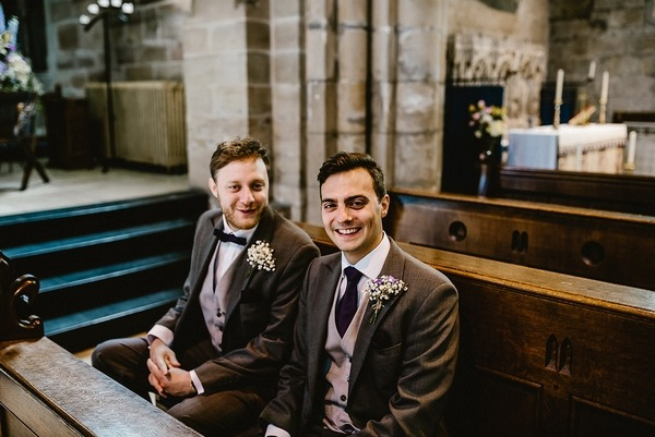 Groom and best man sitting in church before ceremony