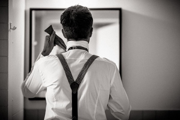 Groom tying bow tie in mirror