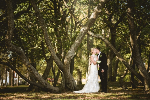 Bride and groom standing by trees - Picture by Natalie Johansson Fotograf