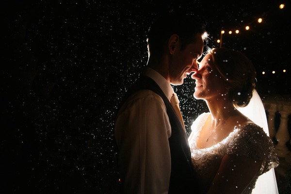 Bride and groom in rain at night - Picture by Stephen McGowan Wedding Photography