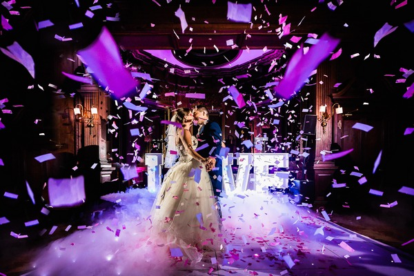 Bride and groom on dance floor with paper confetti falling around them - Picture by Andy Griffiths Photography