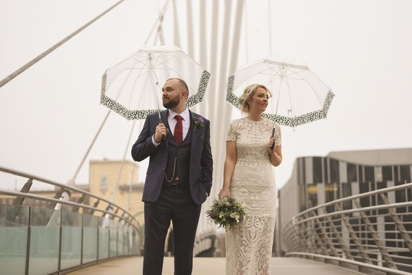 Bride and groom standing on a bridge holding umbrellas - Picture by Rebecca Parsons Photography
