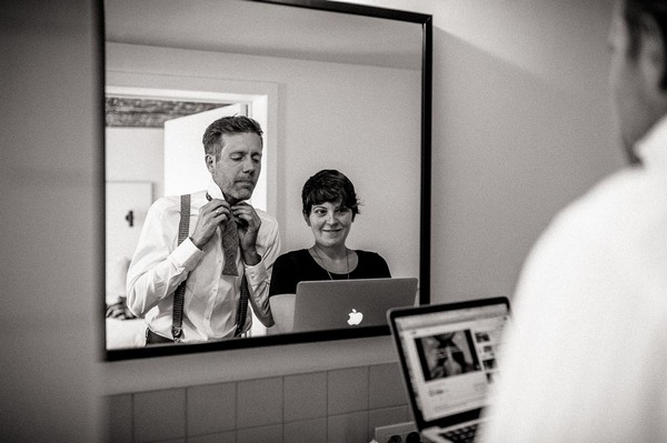 Groom watching video on how to tie a bow tie