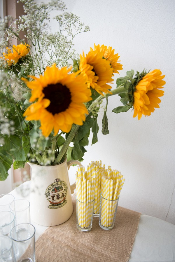 Sunflowers and straws on table