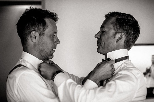 Grooms tying each others bow ties