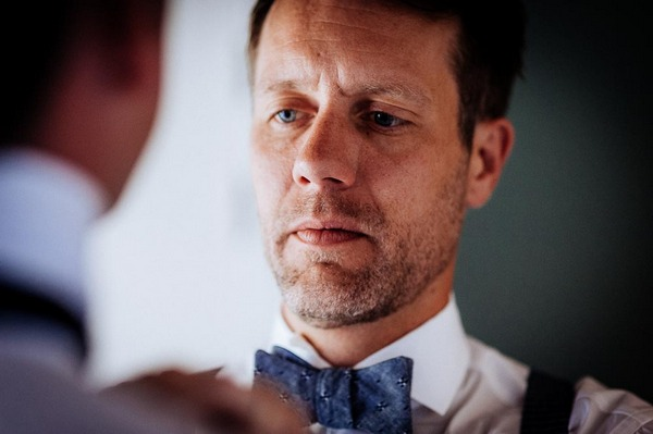 Groom concentrating as he ties bow tie