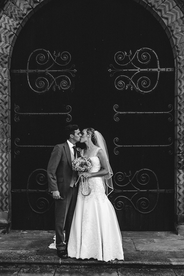 Bride and groom kissing outside church