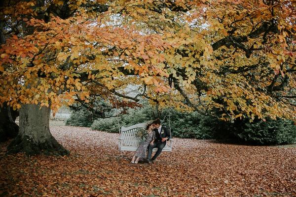 Bride and groom sitting on tree swing