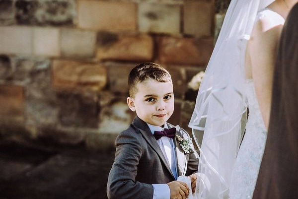 Young boy holding up bride's train on wedding dress