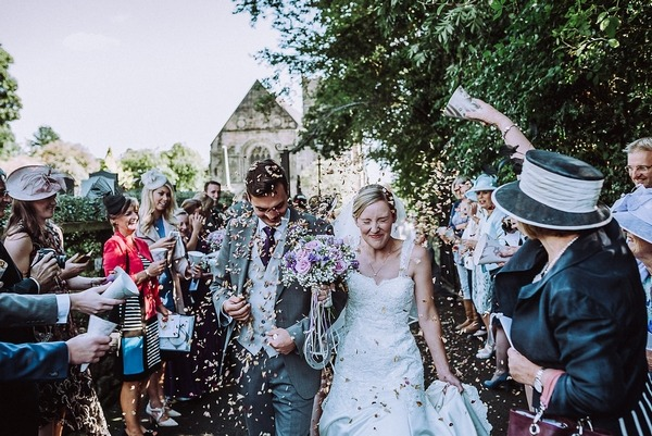 Bride and groom closing eyes as they walk through confetti shower