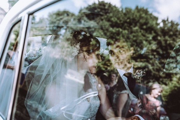 Bride and groom sitting in back of wedding car