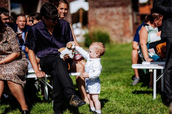 Young child with toy dog at wedding