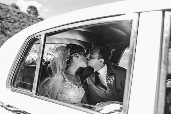 Bride and groom kiss in back of wedding car