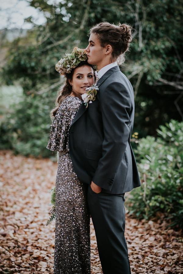 Bride hugging groom under his jacket
